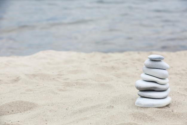 Spa de equilíbrio de pedras zen na praia Foto Premium