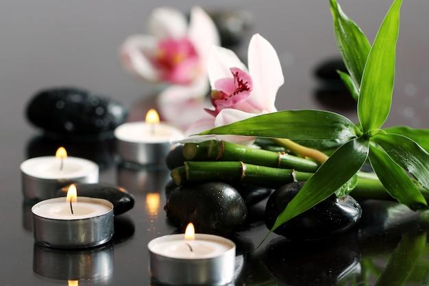 Spa e bem-estar, massagem pedras e flores na toalha de mesa de madeira
