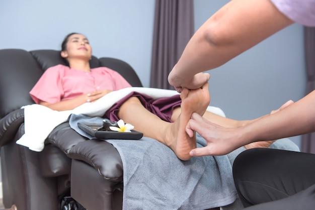 Spa e massagem tailandesa nos pés, belas mulheres relaxantes e saudáveis de aromaterapia