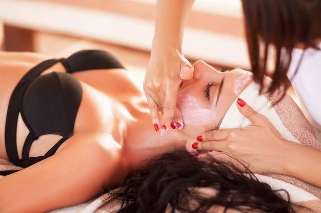 Spa e massagem. uma linda mulher no salão spa na praia ensolarada receber massagem de rosto e costas. alta qualidade.