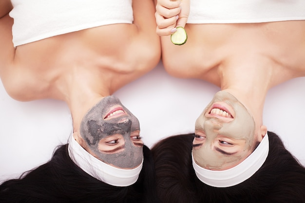 Spa em casa. duas belas moças segurando pedaços de pepino nos olhos e sorrindo enquanto estava na cama