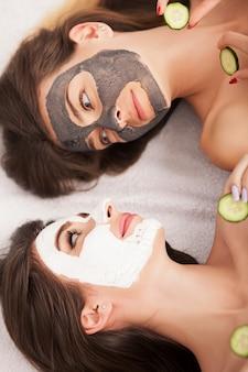 Spa em casa. duas mulheres que prendem partes de pepino em suas faces que encontram-se a cama.