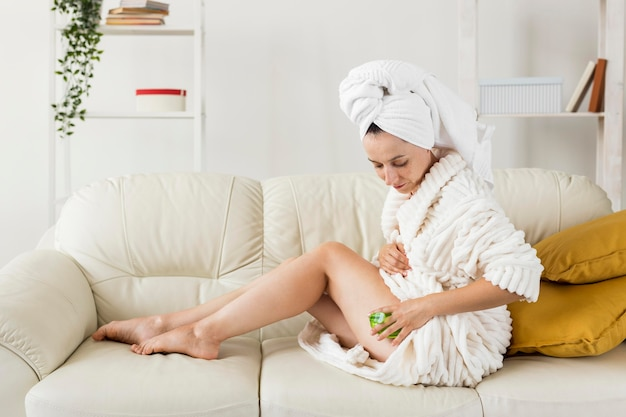 Spa em casa mulher massageando as pernas tiro longo