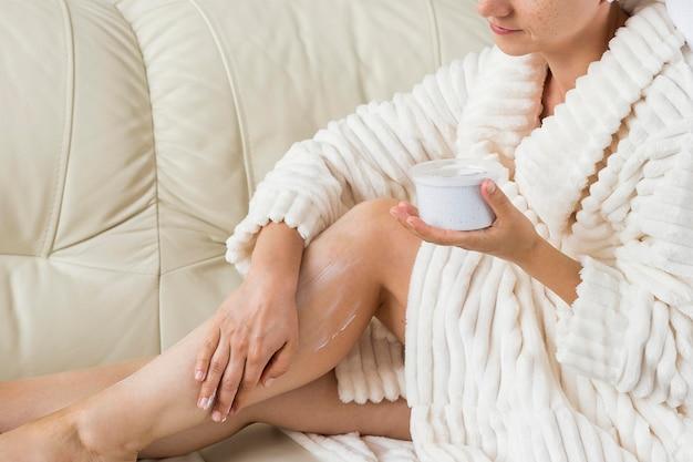 Spa em casa usando creme para hidratar as pernas