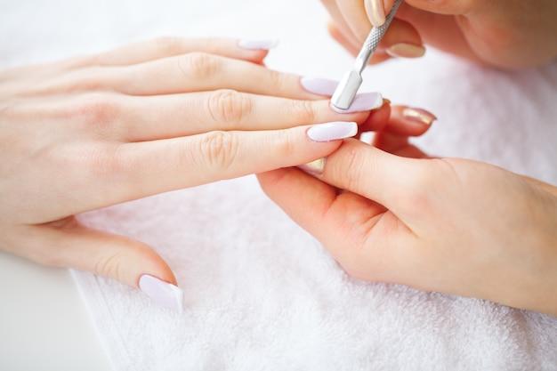 Spa manicure, mulher em um salão de beleza recebendo uma manicure por uma esteticista