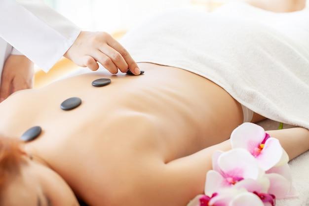 Spa massagem com pedras, mulher bonita, recebendo spa pedras quentes massagem no salão spa