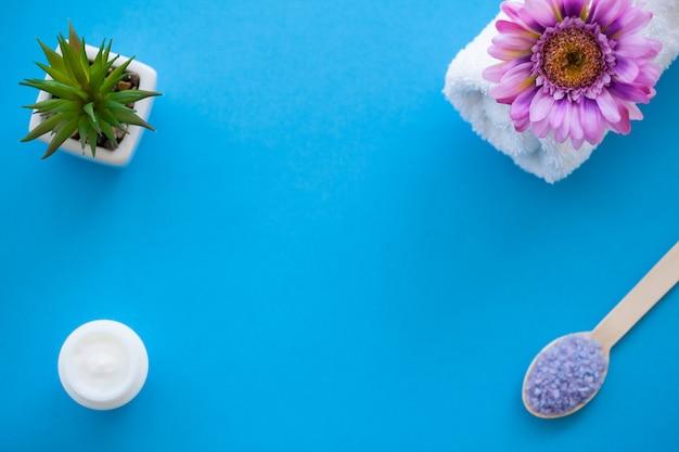 Spa. moagem de sal do mar na luz de madeira - colher de madeira da tabela gasto azul. cozinha e uso saudável cosmética