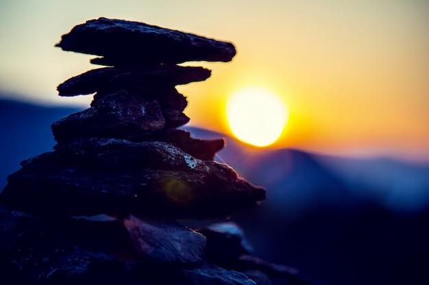 Spa pedras equilíbrio, céu colorido de verão, silhueta de pedras empilhadas e borboleta, bela natureza, pôr do sol praia tranquila, imagem ual de vida estável