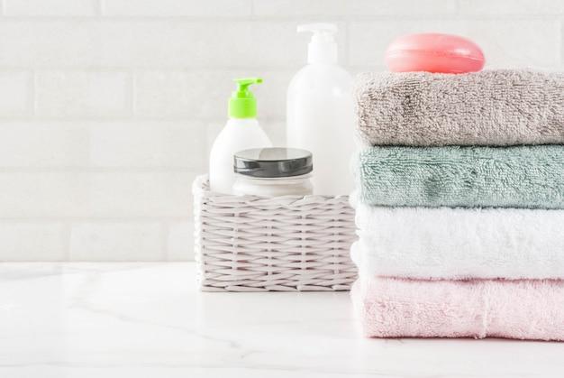 Spa relaxar e banho conceito sal marinho sabão com cosméticos e toalhas no fundo do banheiro branco