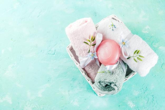Spa relaxar e conceito de banho, sal marinho, sabão, com cosméticos e toalhas na superfície de concreto azul claro