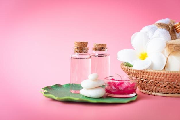 Spa sal do himalaia, vela vermelha, leite e sabão líquido rosa, toalha branca, flores, pedra zen definido nas folhas verdes sobre rosa