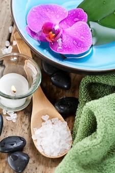 Spa sal e pedras com vela e orquídea