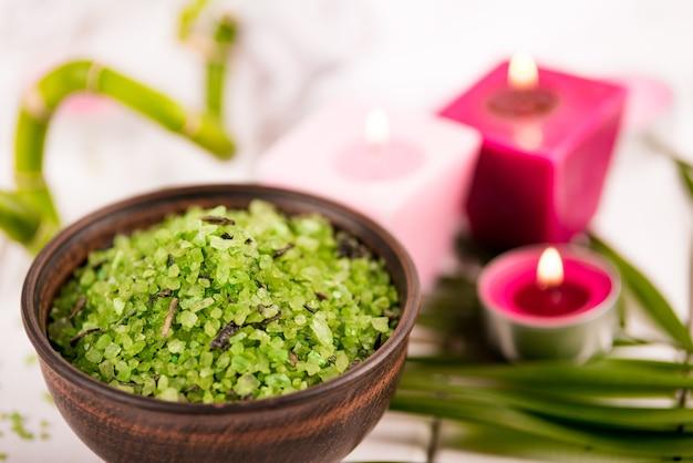 Spa. sal espirulina de ervas verdes em uma tigela de cerâmica, toalhas de spa, vela rosa perfumada e bambu.