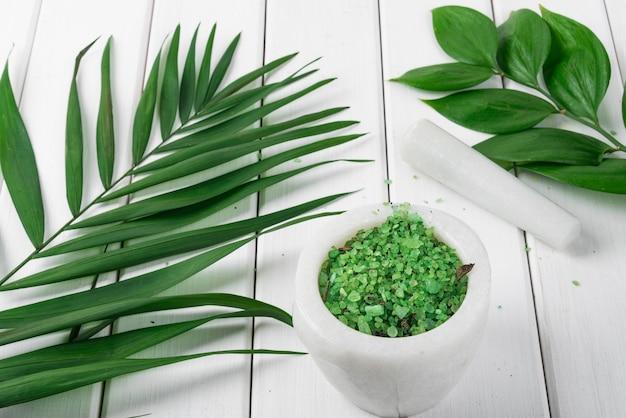 Spa. sal verde de espirulina à base de plantas em almofariz de mármore branco