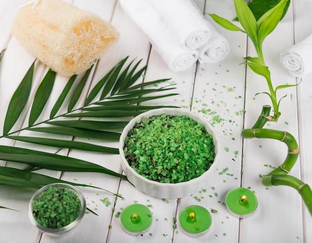 Spa. sal verde de espirulina à base de plantas em uma tigela de cerâmica branca, toalhas de spa, velas e bambu.