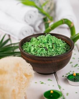 Spa. sal verde de espirulina à base de plantas em uma tigela de cerâmica, toalhas de spa, velas e bambu.