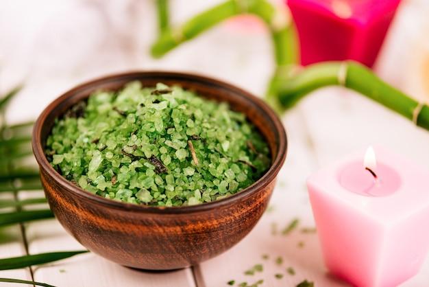 Spa. sal verde de espirulina de ervas em uma tigela de cerâmica, toalhas de spa, vela rosa perfumada e bambu. tonificado, fosco.