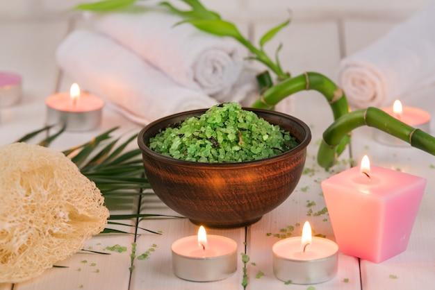 Spa. sal verde de espirulina de ervas em uma tigela de cerâmica, toalhas de spa, vela rosa perfumada e bambu.