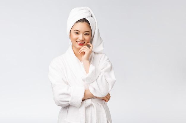 Spa skincare beleza mulher asiática, secar o cabelo com a toalha na cabeça após o tratamento do chuveiro linda jovem multirracial tocando a pele macia