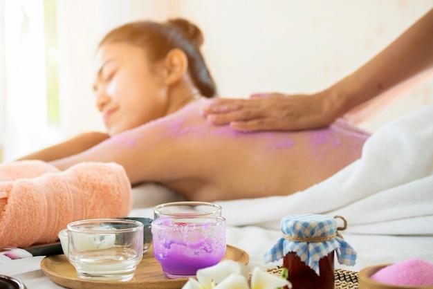 Spa terapeuta esfregar sal nas costas jovem e corpo no salão spa
