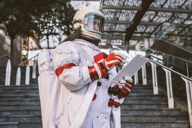 Spaceman em uma estação futurista. homem com traje espacial caminhando em área urbana