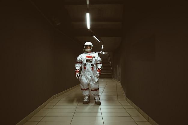 Spaceman em uma estação futurista. homem com traje espacial saindo para o trabalho e pegando o trem
