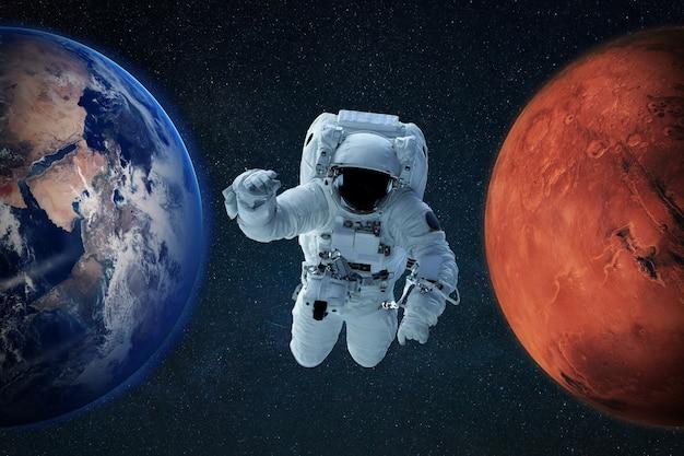 Spaceman no espaço sideral com o planeta azul terra e o planeta vermelho marte. conceito de nova casa. astronauta viaja para novos planetas