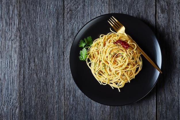 Spaghetti alla colatura di alici, spaghetti com molho de anchova, pimenta, alho e salsa em um prato preto com garfo dourado em uma mesa de madeira escura, vista de cima, postura plana, espaço livre