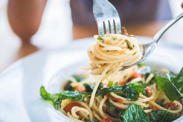 Spaghetti de camarão apimentado e fritado no prato branco com mão da mulher