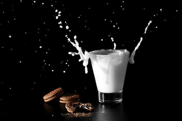 Spalsh em copo de leite e chocolate cookies em fundo preto