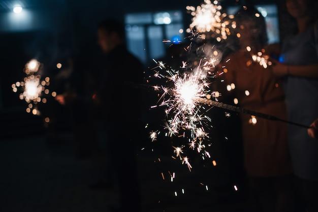 Sparkler brilhantes faíscas na mão de uma pessoa na celebração