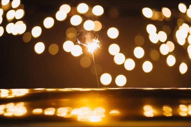Sparkler e luzes sobre a superfície reflexiva
