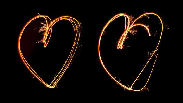 Sparkler luz pintada em forma de dois corações durante a noite
