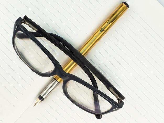 Specs e golden pen no jornal ou notebook