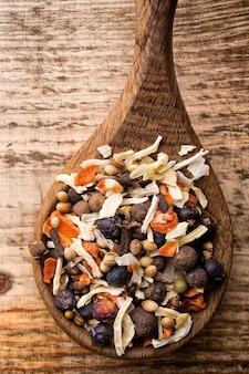Spice misture uma colher de pau em um fundo de madeira.