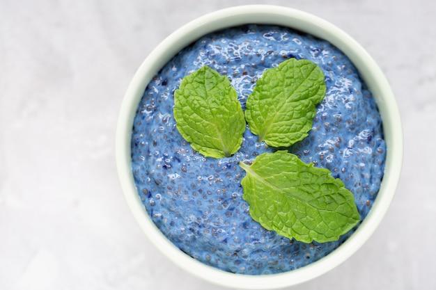 Spirulina azul ou ervilha de borboleta azul matcha em pó pudim de sementes de chia em tigela de porcelana.