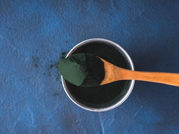 Spirulina em pó na colher em fundo azul