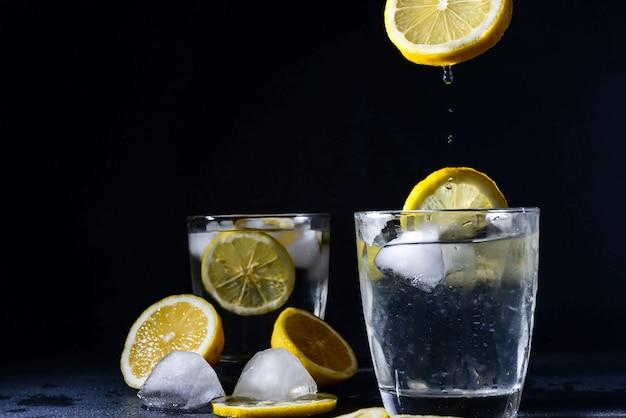 Splash cocktail de gim e tônica com fatias de limão cubo de gelo cai na água com limão copie o espaço, limonada