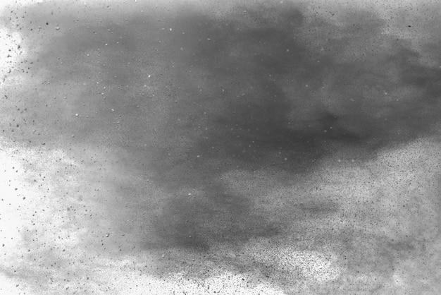 Splatter preto das partículas no fundo branco. pó de pó preto explodindo.