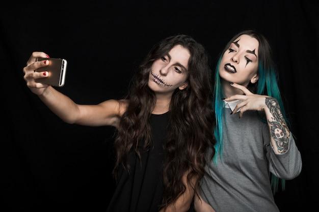 Spooky mulheres jovens tomando selfie