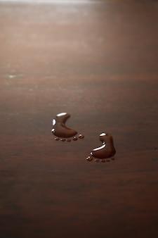 Spoor footmark por gotas de água da arte no fundo da mesa de madeira.