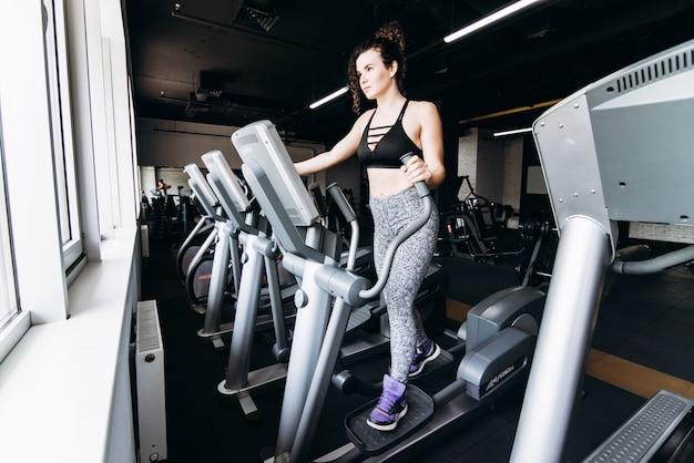 Sportista de fitness em roupas esportivas de moda corrida na academia, fazendo exercícios cardio. vestuário e sapatos esportivos, estilo urbano.