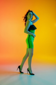 Sportive. linda garota sedutora em maiô elegante em fundo gradiente laranja em luz de néon.