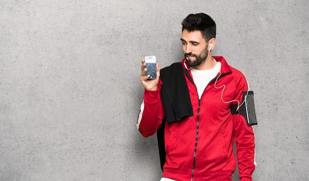 Sportman bonito com perturbada exploração smartphone quebrado sobre parede texturizada