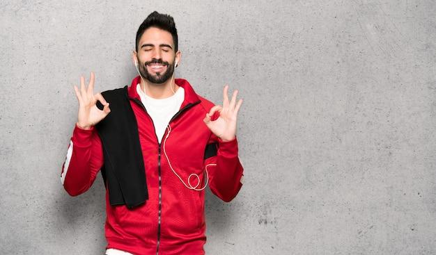 Sportman bonito em zen posar sobre parede texturizada