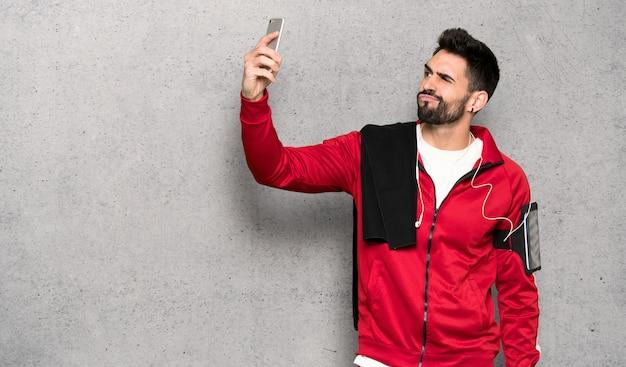 Sportman bonito fazendo um selfie sobre parede texturizada