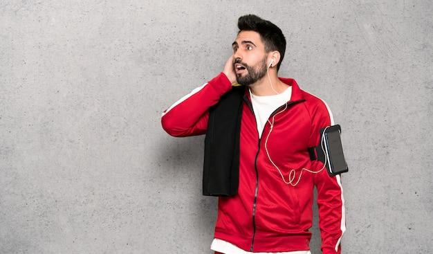 Sportman bonito pensar uma idéia enquanto coçando a cabeça sobre a parede texturizada