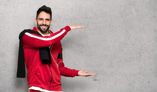 Sportman bonito segurando copyspace para inserir um anúncio sobre parede texturizada