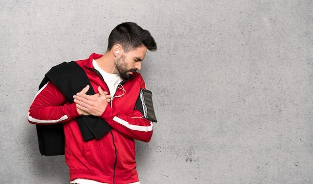 Sportman bonito tendo uma dor no coração sobre parede texturizada