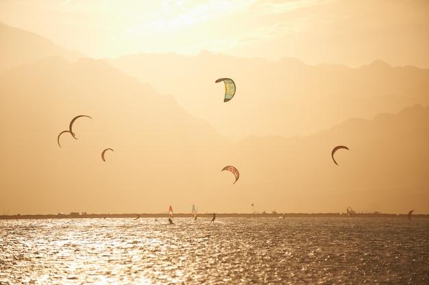 Sportmans kitesurf na superfície do mar contra montanhas na hora por do sol